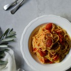 Σπαγγέτι με Ντοματίνια και Ελαιόλαδο www.thefoodiecorner.gr. Spaghetti cooked with cherry tomatoes, served on a pretty white plate. Plate with fork and spoon sitting on a marble surface with a few branches from an olive tree and a muslin cloth to decorate.