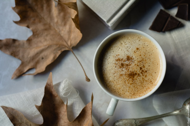 Pumpkin Spice Latte, Καφές Λάτε με Γεύση Κολοκύθας και Μπαχαρικών www.thefoodiecorner.gr 03 Photo description: One cup of psl next to dry autumn leaves, sitting on marble-like surface. A few pieces of dark chocolate visible in the top right corner.
