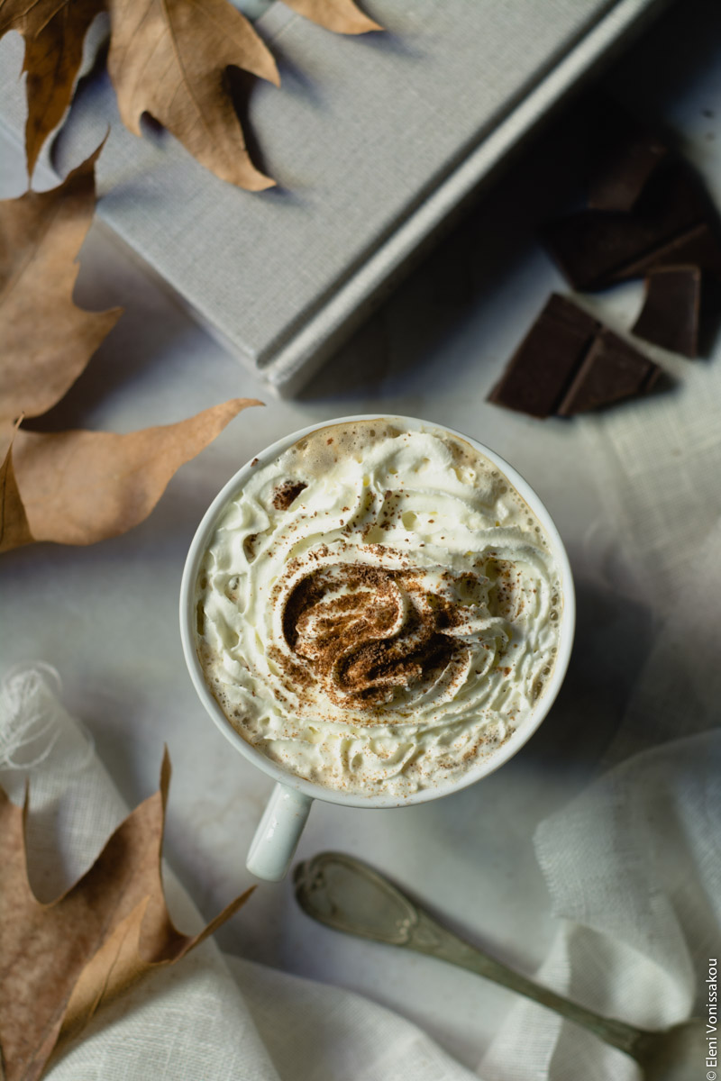 Pumpkin Spice Latte, Καφές Λάτε με Γεύση Κολοκύθας και Μπαχαρικών www.thefoodiecorner.gr 06 Photo description: A closer look at one of the cups of psl with whipped cream and a sprinkling of spices and shaved chocolate. Dry leaves to the left and the handle of an old silver spoon towards the bottom.