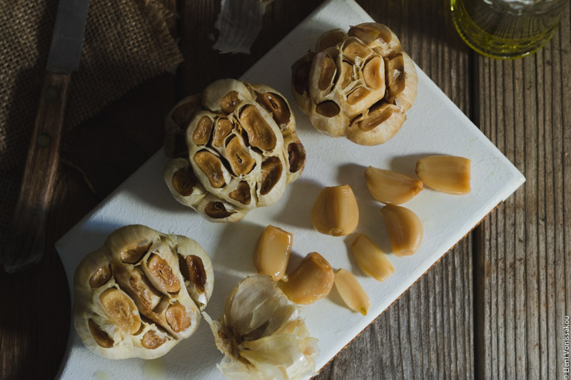 Slow Cooker Roasted Garlic www.thefoodiecorner.gr 04 Photo description: Roasted garlic bulbs on a white chopping board, one of them empty with the golden cloves lying next to it.