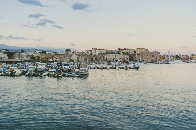 Food Styling and Photography Retreat – Crete, Greece 2017 www.thefoodiecorner.gr Photo description: A view from across the harbour of the old town of Chania, the fishing boats in the marina and the calm sea.