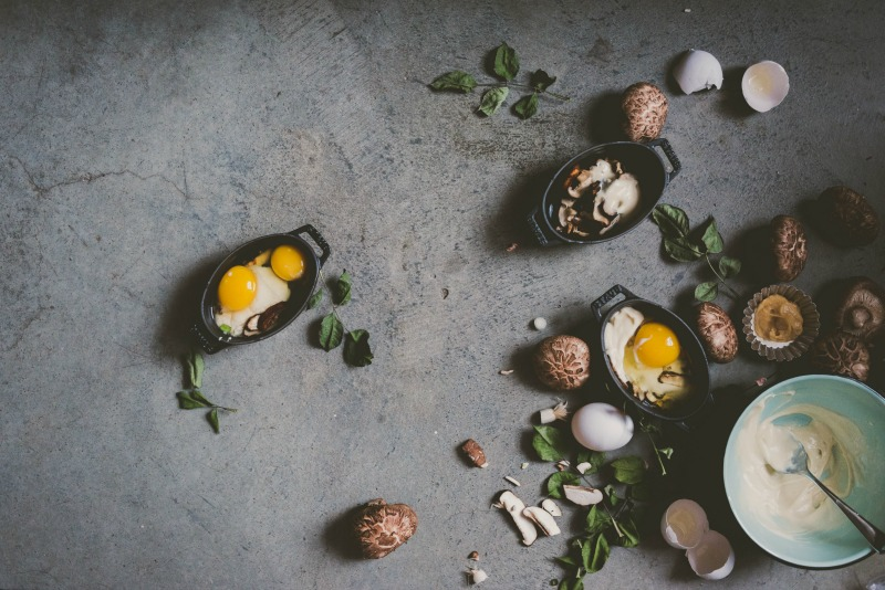 Food Styling and Photography Retreat – Crete, Greece 2017 www.thefoodiecorner.gr Photo description: Pictured to the right of the photo are some mini baking dishes with raw eggs in them, surrounding the dishes are mushrooms, eggs and greens. In the corner a bowl with a white sauce. All on a grey slate-like background.