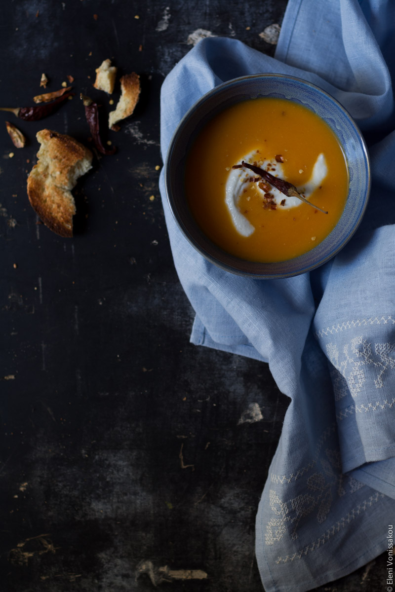 Butternut Squash Soup with Chilli and Whipped Goat's Yoghurt Feta www.thefoodiecorner.gr Photo description: Overhead view of one blue bowl of butternut squash soup, in the top right corner of the frame, sitting on a light blue linen tea towel on a dark surface. The linen extends towards the bottom of the photo. On the soup is a swirl of whipped feta and a chilli pepper. To the left of the bowl is a broken piece of toasted bread.