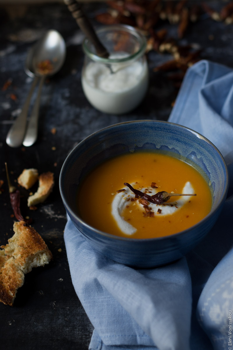 Butternut Squash Soup with Chilli and Whipped Goat's Yoghurt Feta www.thefoodiecorner.gr Photo description: A 3/4 side view of one blue bowl of butternut squash soup, sitting on a light blue linen tea towel. A swirl of whipped feta and a chilli pepper sit on top of the soup. Behind the bowl is a small jar of whipped feta with a wooden handle spoon sitting in it. To the left of the bowl are some pieces of broken toasted bread. Right at the top a slightly blurred view of spoons and some whole dried chilli peppers.