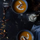 Butternut Squash Soup with Chilli and Whipped Goat's Yoghurt Feta www.thefoodiecorner.gr Photo description: Overhead view of two bowls of butternut squash soup, one on each end of a dark surface. Around them along the edges are spoons, chilli flakes, whole dried chilli peppers and bits of toasted bread. In the bottom right corner is a light blue linen tea towel. On the right a small jar of whipped feta with a wooden handle spoon. On top of the bright orange soup is a swirl of whipped feta and a chilli pepper.