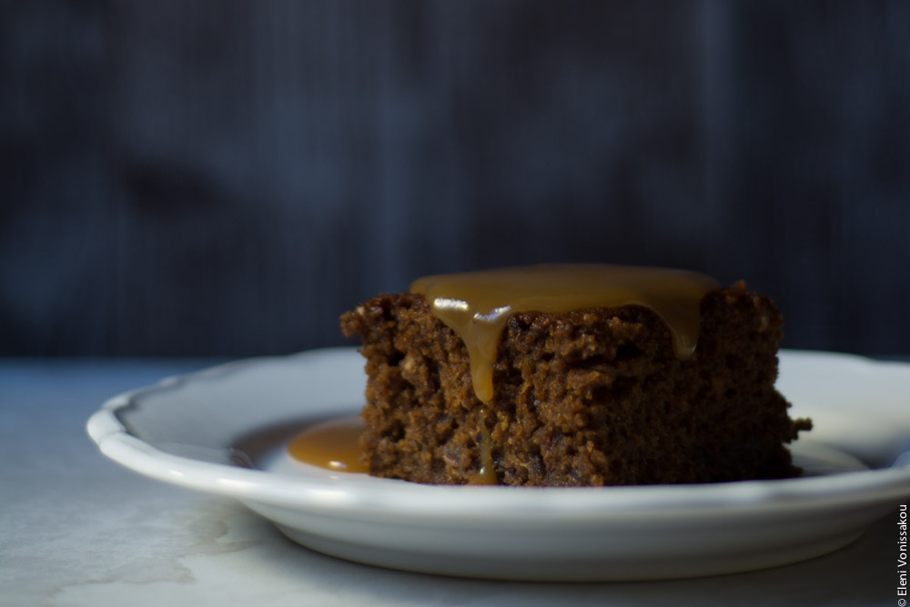 Sticky Toffee Pudding Κέικ με Χουρμάδες και Σάλτσα Καραμέλας Βουτύρου www.thefoodiecorner.gr Photo description: Side view of a plate with a piece of sticky toffee pudding on it, sauce running down the sides, in front of a dark background.