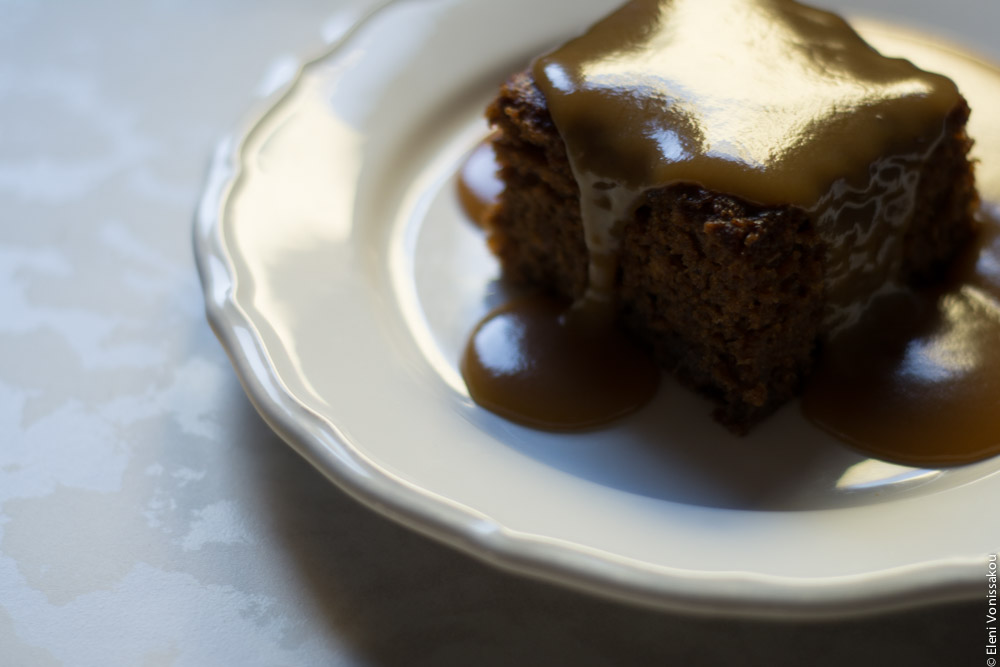 Chai Carob Sticky Toffee Pudding www.thefoodiecorner.gr Photo description: A piece of sticky toffee pudding with sauce all over it and down the sides, sitting on a white plate, light coming from behind darkening the front of the cake and making the sauce shine on top.