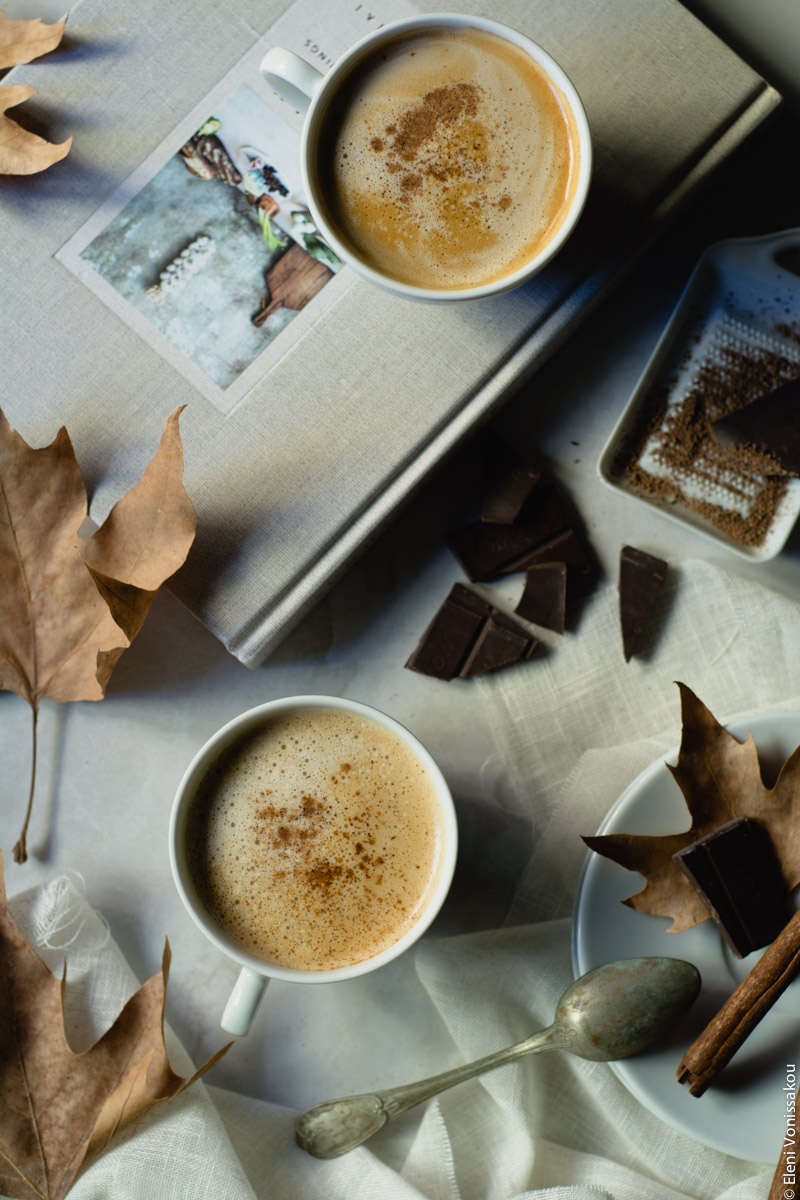 Food Styling and Photography Retreat – Crete, Greece 2017 www.thefoodiecorner.gr Photo description: Two cups of coffee on a marble like background, one sitting on a similar coloured book. Around them dry autumn leaves, some pieces of dark chocolate and a grater, and a cinnamon stick on a saucer.