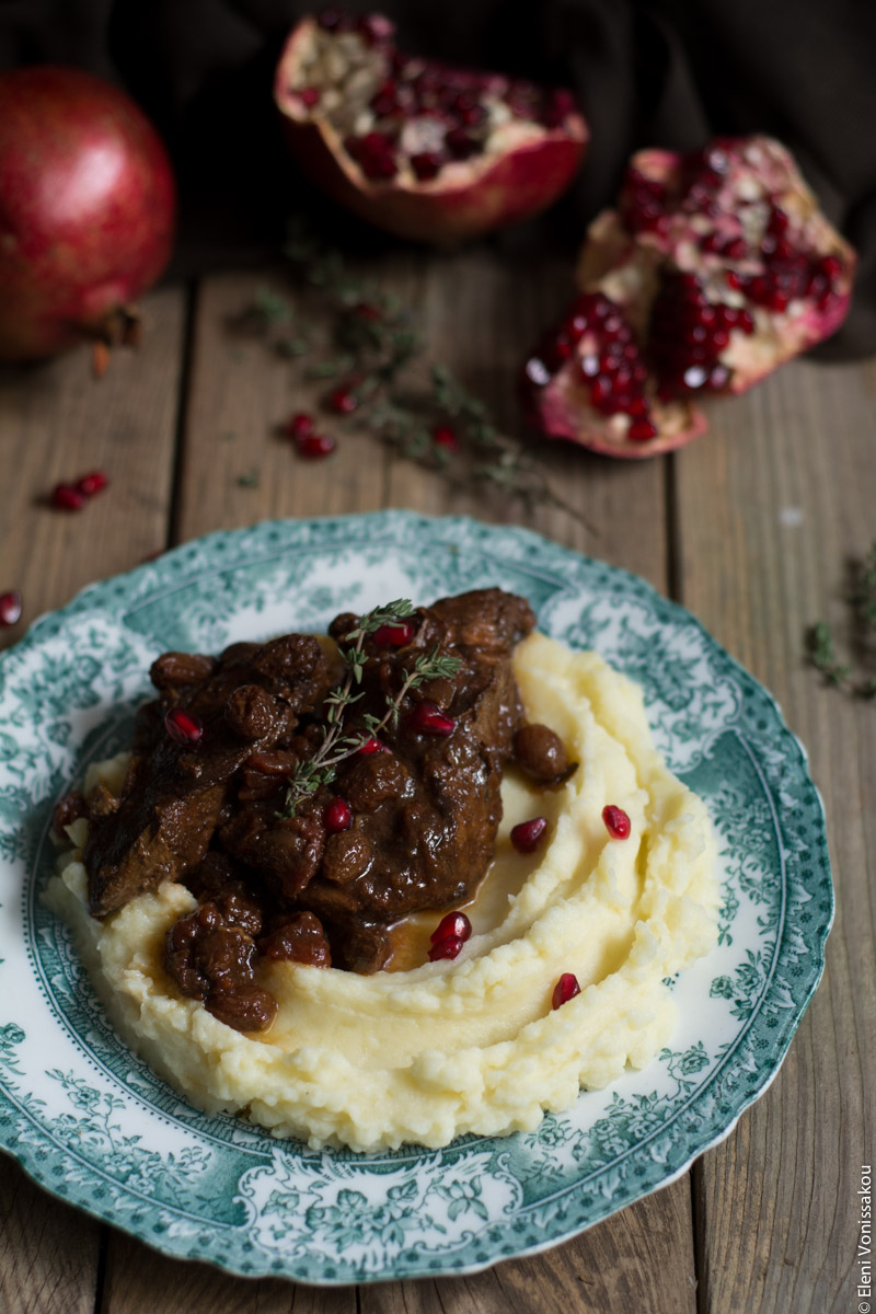 Slow Cooker Pomegranate and Tomato Beef with Sultanas www.thefoodiecorner.gr Photo description: Three quarter view of a plate of beef over mashed potatoes with some pomegranate arils sprinkled on top. The antique plate has a pretty design around the edge and is sitting on a wooden background. Behind the plate are some pomegranates, one of them broken open to reveal the arils inside. A couple of sprigs of thyme decorate the meat.