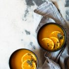 Simple Slow Cooker Carrot and Orange Soup with Turmeric and Cumin www.thefoodiecorner.gr Photo description: Two black bowls with carrot and orange soup, on a grey and white marble surface. One bowl is sitting on a grey linen dish cloth. Both bowls have a garnish of orange slices, a coriander leaf and some nigella seeds.