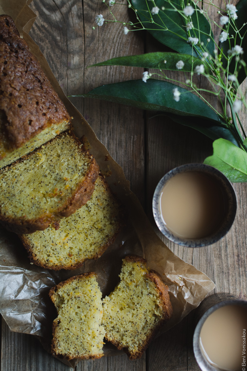 Sticky Orange Poppy Seed Olive Oil Loaf Cake www.thefoodiecorner.gr Photo description: The cake lying diagonally from top left to the centre of the photo. The main part is only partly visible, and there are two whole slices lying in front. Further down is one slice broken in two. To the right of the cake are two metal cups with tea in them. In the top right corner some orange leaves and small white flowers.