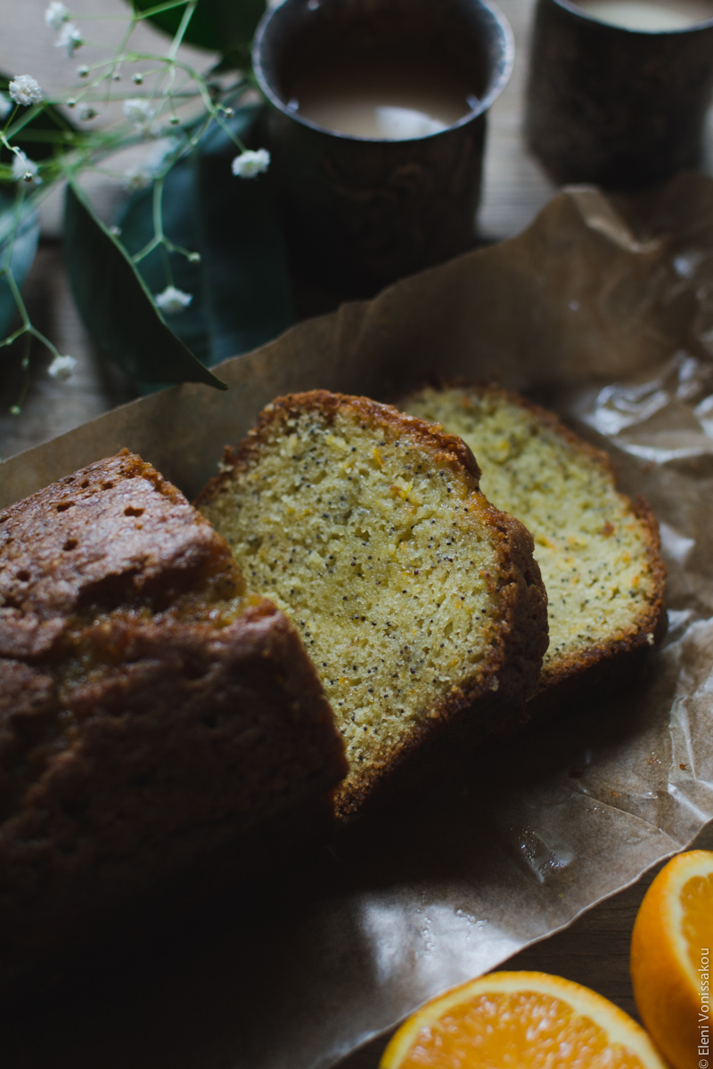 Sticky Orange Poppy Seed Olive Oil Loaf Cake www.thefoodiecorner.gr Photo description: A close view of the top half of the cake, with two cut slices lying in front of it. Cake is on brown baking paper. To the top of the photo two metalic cups with tea and a couple of leaves from an orange tree. To the bottom of the photo barely visible, two halves of an orange.
