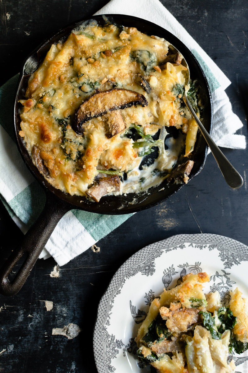 Pasta Bake with Spinach and Portobello Mushrooms in Bechamel Sauce www.thefoodiecorner.gr Photo description: To the top of the photo, the skillet with the pasta bake, a spoon lying inside and a piece missing. To the bottom right, a plate with a pretty pattern round the edge, with a messy piece of pasta bake on it. Some penne coated with creamy béchamel are visible, as well as some spinach and pieces of golden crunchy topping.