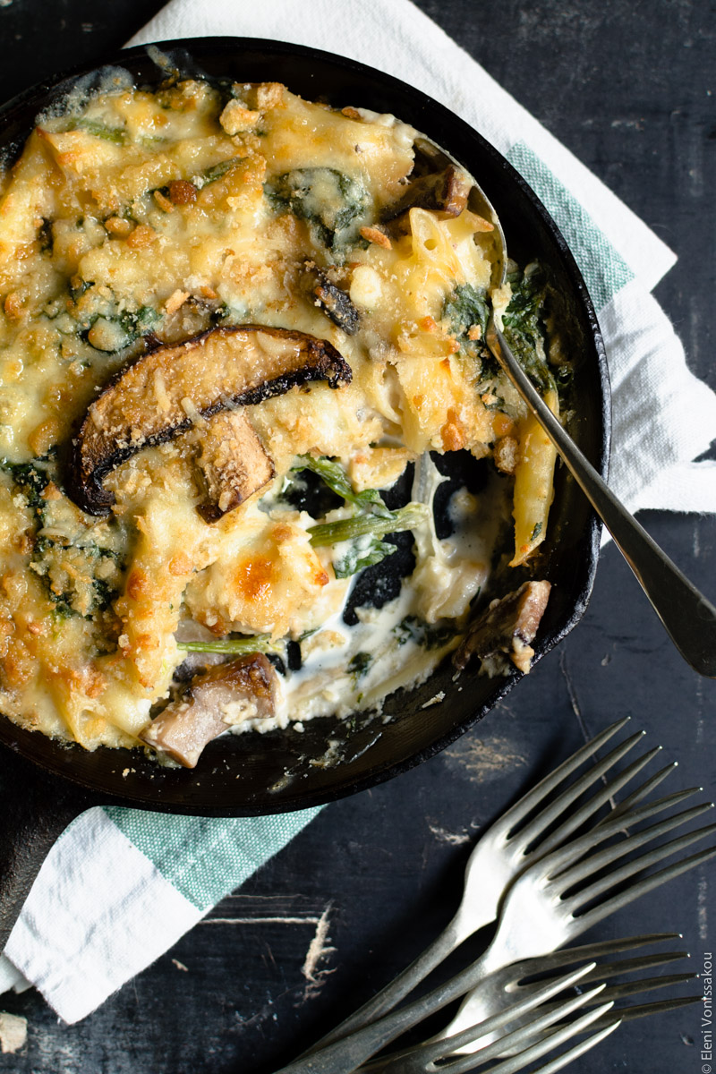 Pasta Bake with Spinach and Portobello Mushrooms in Bechamel Sauce  www.thefoodiecorner.gr Photo description: A close up of the skillet with a spoon lying in it. A piece of pasta bake has been taken out and some pieces of spinach, mushrooms and creamy bechamel are visible from within. To the bottom right a bunch of forks. The skillet is on the folded tea towel.