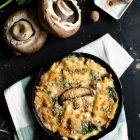 Pasta Bake with Spinach and Portobello Mushrooms in Bechamel Sauce www.thefoodiecorner.gr Photo description: A black cast iron skillet with a golden crunchy topped pasta bake, sitting on a folded linen tea towel. To the top left are two Portobello mushrooms lying stalk-up and some spinach leaves, to the centre are some raw penne pasta pieces, and to the right is a small porcelain grater with some nutmeg on it. All on a black rough and slightly battered surface.
