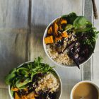 Roast Beetroot and Sweet Potato Buddha Bowl with Spicy Tahini Honey Dressing www.thefoodiecorner.gr Photo description: Two Buddha bowls sitting on a piece of linen material with a stripe running down the right side. To the bottom right of the photo a small bowl of dressing with a spoon in it, and to the top right a small bowl with sunflower seeds and a spoon in it. The ingredients are placed in each quarter of the bowls - greens in one, rice in another, beetroot and sweet potato in the other two quarters. Sprinkled on top are dried cranberries and sunflower seeds. Some dressing is drizzled over everything.