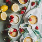 Easy Baked Lemon Puddings www.thefoodiecorner.gr Photo description: Top view of five lemon puddings in white ramekins, spread out on a light green wooden surface. Two of them are sitting on a scrunched up linen tea towel. Scattered here and there between the ramekins are whole strawberries and camomile flowers. At the top of the photo is a small sieve with icing sugar, and to the left are one whole and one half lemon. Near that, a bowl of mascarpone cheese with some strawberries on top. The puddings have sprinkled icing sugar and some strawberries on them.