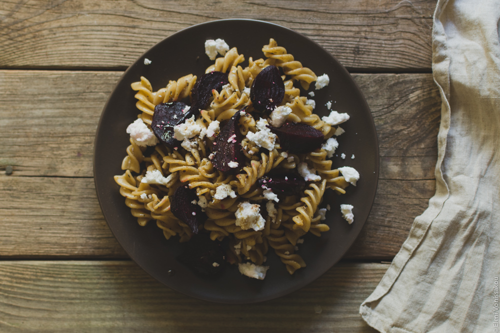 Roast Beetroot and Feta Pasta Salad with Greek Yoghurt and Cumin Dressing www.thefoodiecorner.gr Photo description: The plate of pasta salad, with fusilli shaped pasta and chunks of beetroot and crumbled feta. The plate is sitting on a wheather beaten wooden surface. To the right of the photo a beige linen napkin just visible.