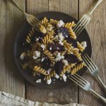 Roast Beetroot and Feta Pasta Salad with Greek Yoghurt and Cumin Dressing www.thefoodiecorner.gr Photo description: a brown plate of fusilli pasta salad on a weather beaten wooden surface. At the bottom of the photo, a linen napkin just visible. Around the plate, four forks are propped face down against the edge.