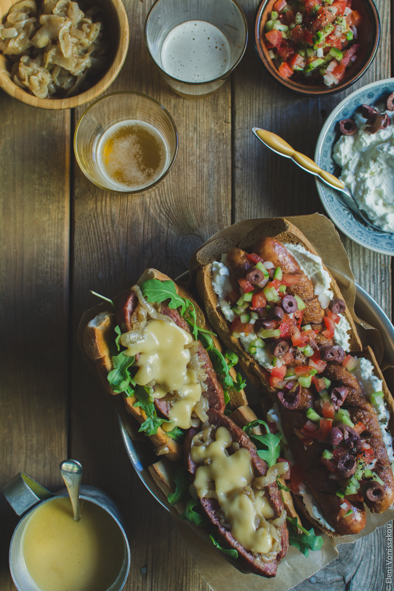 Two Ways with Greek Sausage Hot Dogs www.thefoodiecorner.gr - Photo description: A top view of the plate of hot dogs, this time with four (2 of each flavour) arranged on the baking paper. The plate is positioned to the bottom right, and the condiments and beers are in the top of the photo. Only the cheese sauce is in the bottom left corner.