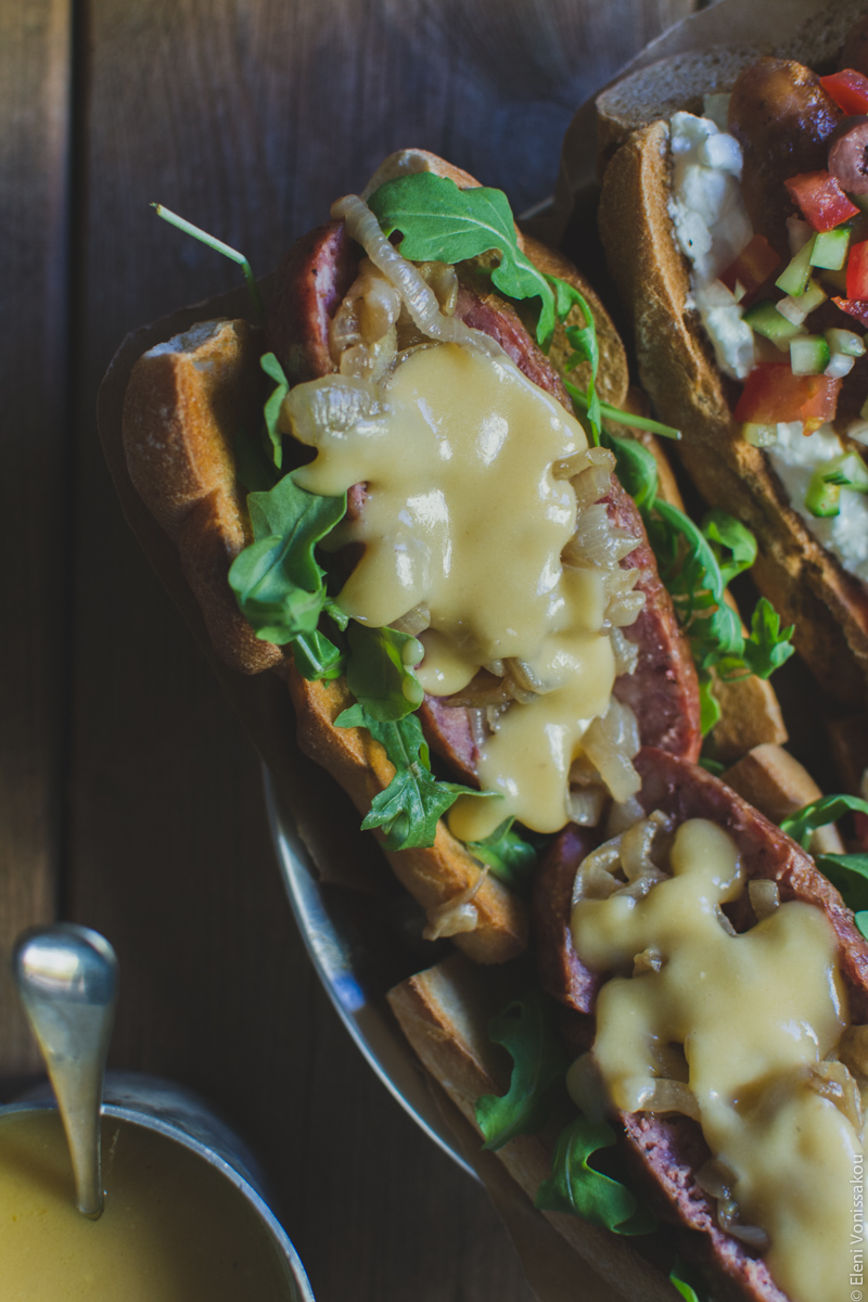 Two Ways with Greek Sausage Hot Dogs www.thefoodiecorner.gr - Photo description: A closer view of one of the hot dogs, with rocket, caramelised onions and beer cheese sauce on top.