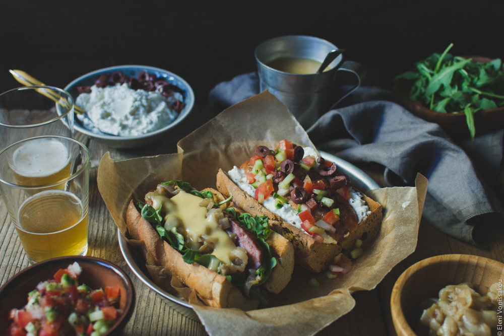 Two Ways with Greek Sausage Hot Dogs www.thefoodiecorner.gr - Photo description: A ¾ view of the plate of hot dogs. The bowls of condiments are arranged around it together with a couple of glasses of beer. Everything is on an old wooden surface set against a dark backdrop.