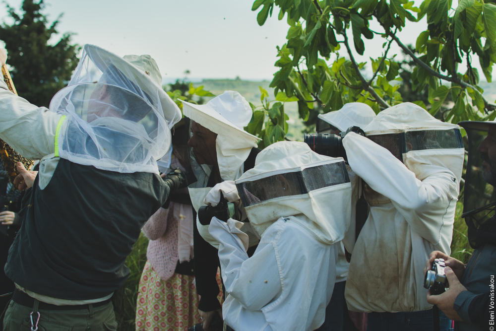 Miliaworkshop2017 www.thefoodiecorner.gr Photo description: Side view of several people in bee hive suits, all hunched together taking photos of a subject not in view.