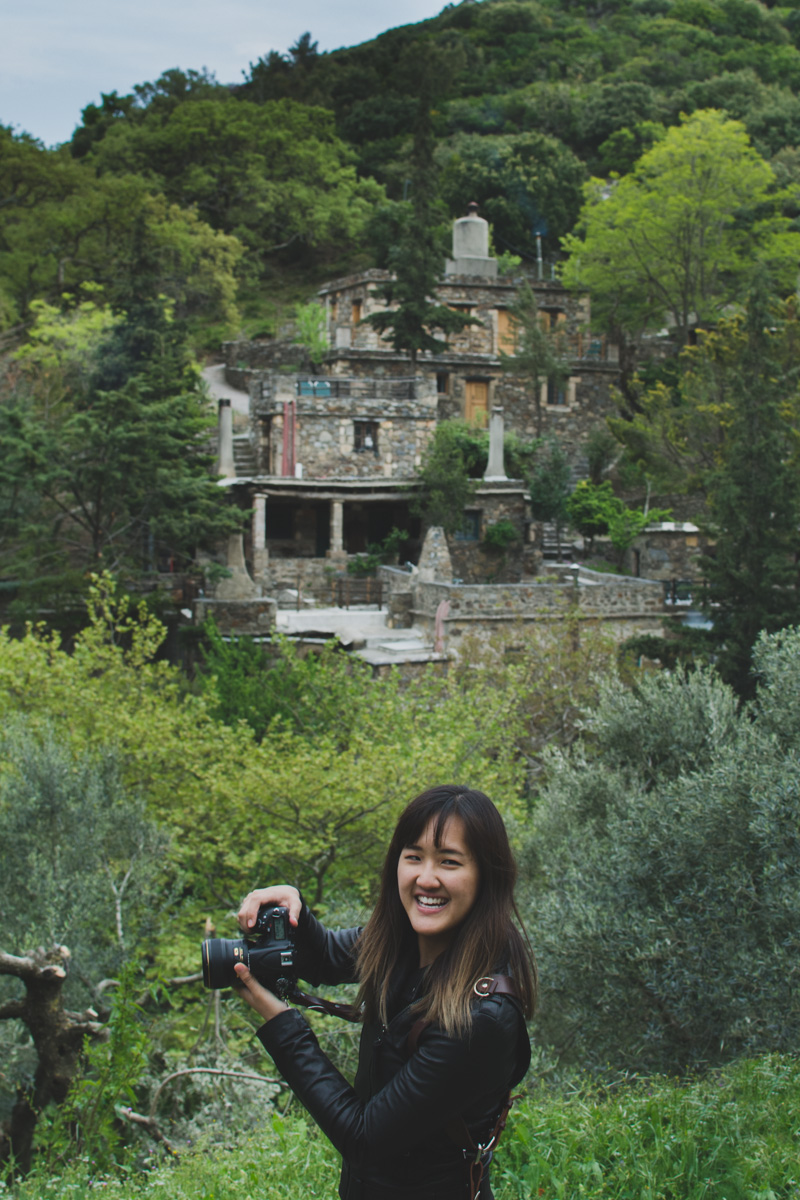 Milia Workshop 2017 – A long overdue recap. Part 1. www.thefoodiecorner.gr - Photo description: A young lady standing sideways with her face turned to the camera. She is holding her own camera aimed in front of her. In the background, the stone buildings of Milia among green trees and bushes.