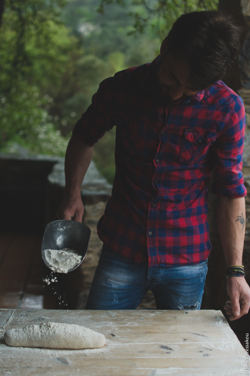 Miliaworkshop2017 www.thefoodiecorner.gr Photo description: Front view of a young man in jeans and a checked shirt, standing behind a wooden table, sprinkling flour from a metal scoop over some dough shaped into a loaf.
