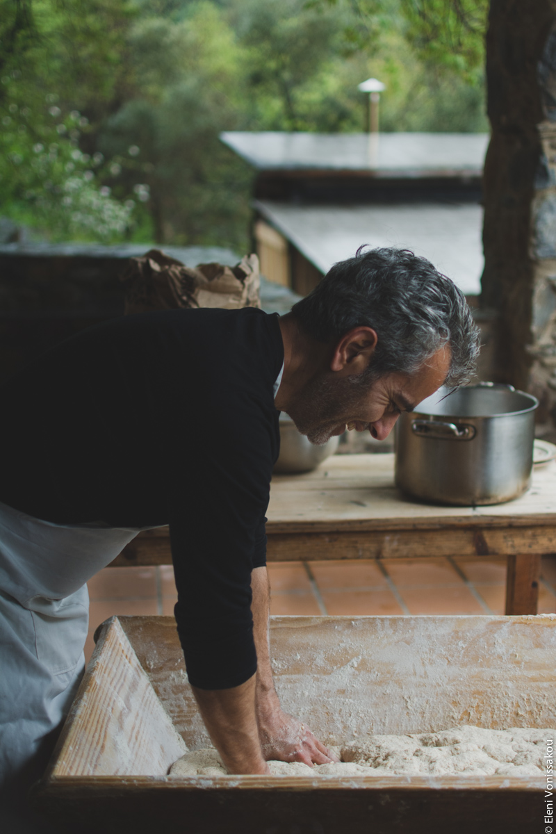 Miliaworkshop2017 www.thefoodiecorner.gr photo description: Side view of a man, apron on, sleeves rolled up, bending over a large wooden basin filled with dough. In the background some trees and the roof of an outbuilding.