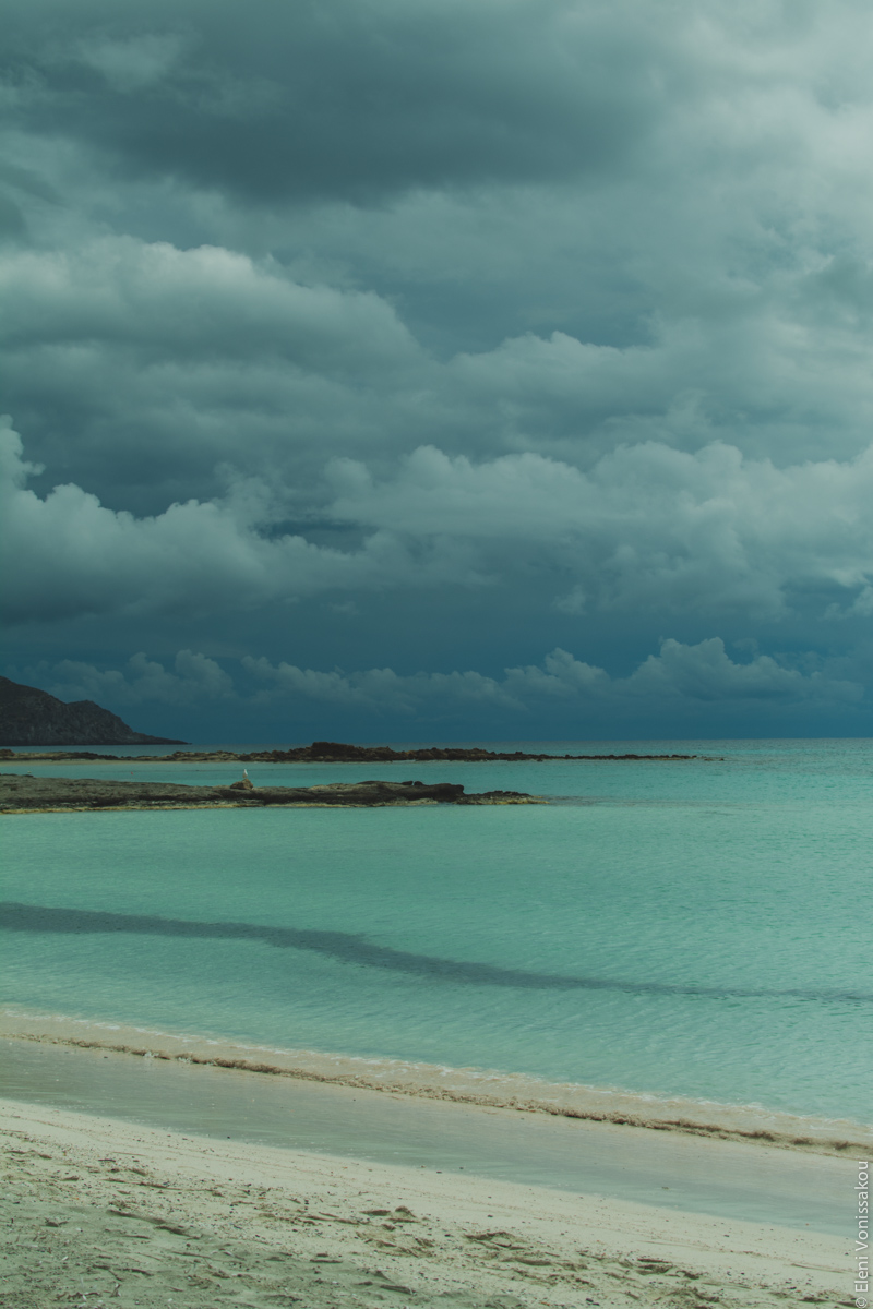 Miliaworkshop2017 www.thefoodiecorner.gr Photo description: The beach and sea, with light coloured sand, turquoise waters and a dramatic sky with dark heavy clouds in the distance.