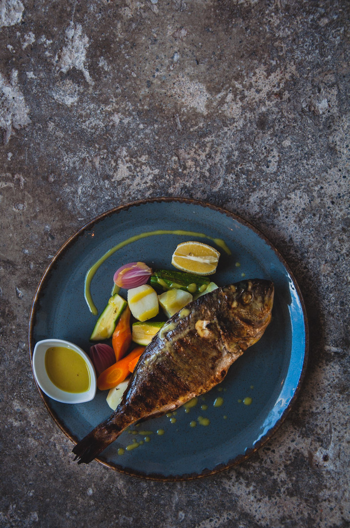 Miliaworkshop2017 www.thefoodiecorner.gr Photo description: a whole, cooked fish lying across a round plate. Underneath it, some boiled potatoes, courgettes and carrots, a wedge of lemon and a small bowl of yellow sauce. Plate is on a rough concrete surface.