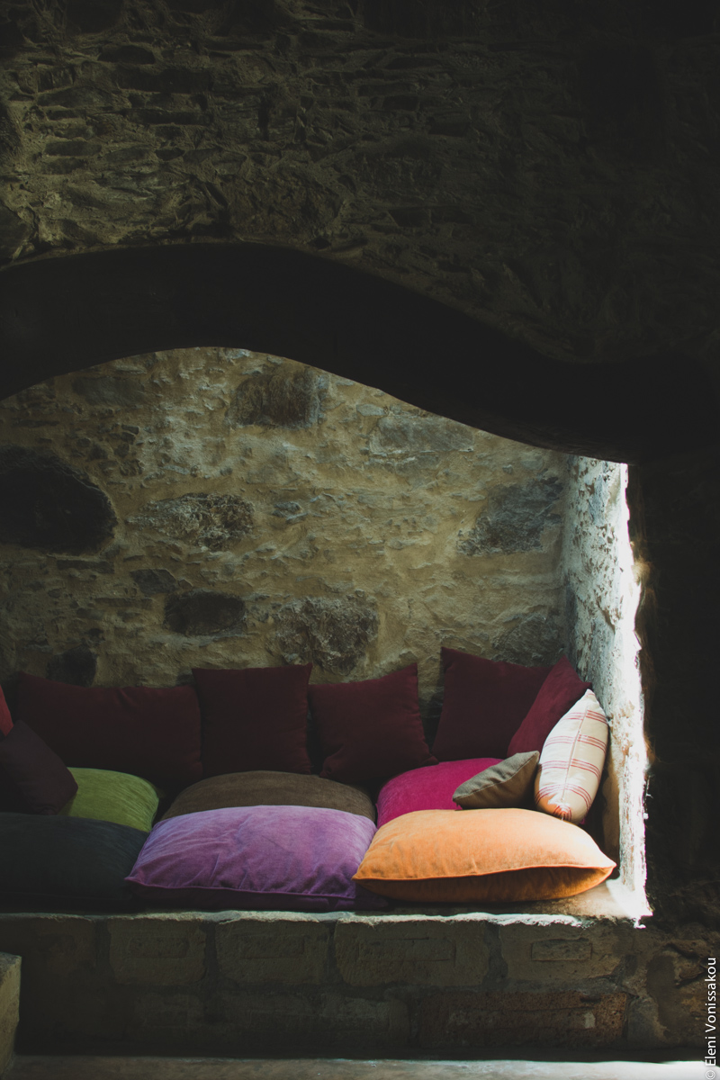 Milia Workshop 2017 – A long overdue recap. Part 1. www.thefoodiecorner.gr - Photo description: An inlet in a stone wall made into a sitting area with large colourful cushions. Light comes down from a skylight.