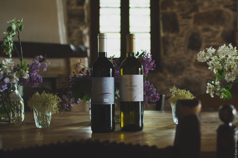 Miliaworkshop2017 www.thefoodiecorner.gr Photo description: two bottles of Dourakis wine on a big wooden table, among several vases with flowers. In the background a stone wall and a window with a wooden pane.