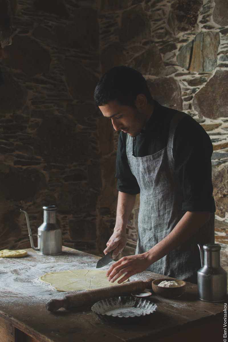 Miliaworkshop2017 www.thefoodiecorner.gr Photo description: A ¾ side view of a young man cutting some rolled out pastry. The wooden table is covered in flour and on it is a rolling pin and some metal canisters. The man is standing in front of a stone wall.