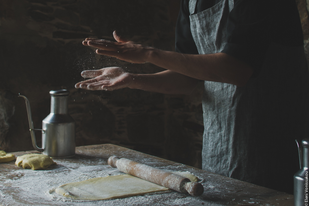 Miliaworkshop2017 www.thefoodiecorner.gr Photo description: A table with some rolled out dough and a rolling pin on it, and an open pair of hands mid air looking as if they have just been clapped together. Particles of flour are visible flying around in between the hands.