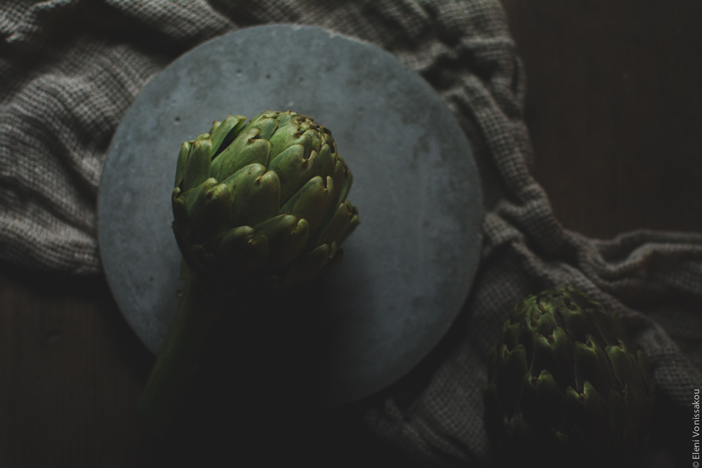 Miliaworkshop2017 www.thefoodiecorner.gr Photo description: an artichoke sitting on a cement plate, the low light reflecting off the top of it. The plate is on a bunched up muslin-type piece of material.