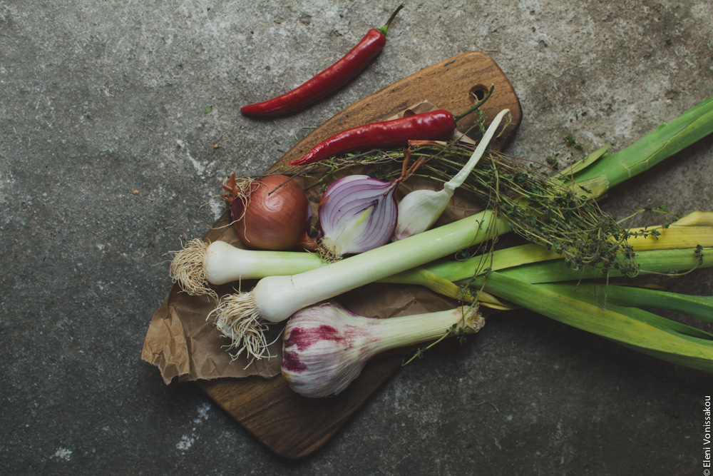 Miliaworkshop2017 www.thefoodiecorner.gr Photo description: a wooden chopping board with onions, leeks, peppers and herbs on it, all on a cement surface.