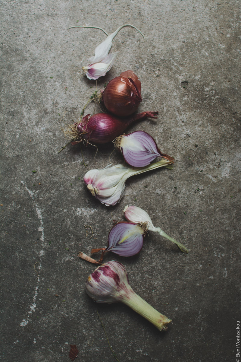 Milia Workshop 2017 – A long overdue recap. Part 1. www.thefoodiecorner.gr - Photo description: Red onions and fresh garlic laid out in a vertical line on a rough gray surface. Some of the onions are cut in half.