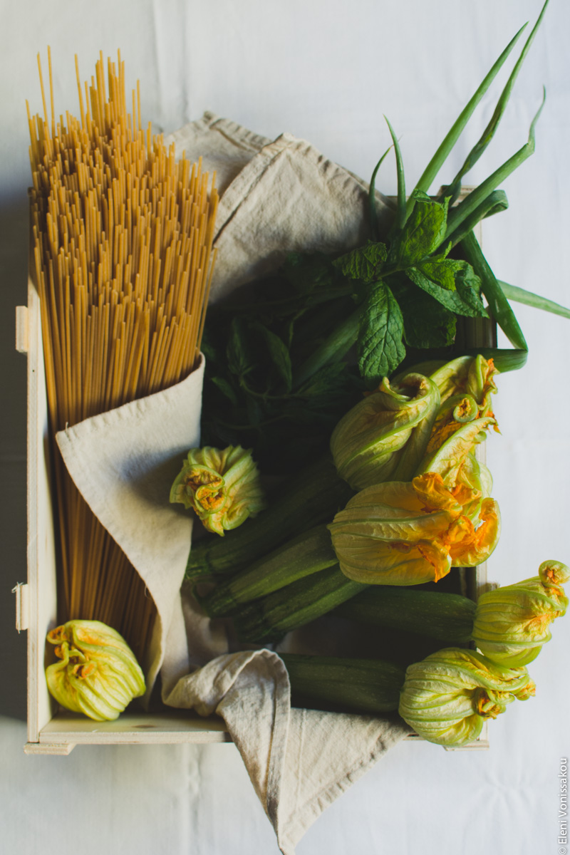 Whole Wheat Courgette Pasta with Courgette Flowers www.thefoodiecorner.gr Photo description: An open wooden box lined with a linen tea towel, containing whole courgettes with their flowers, propped up against the right side. There is also a bunch of spring onions and some sprigs of spearmint in the box next to the courgettes. Lying in the box on its left side, is some uncooked whole wheat spaghetti.