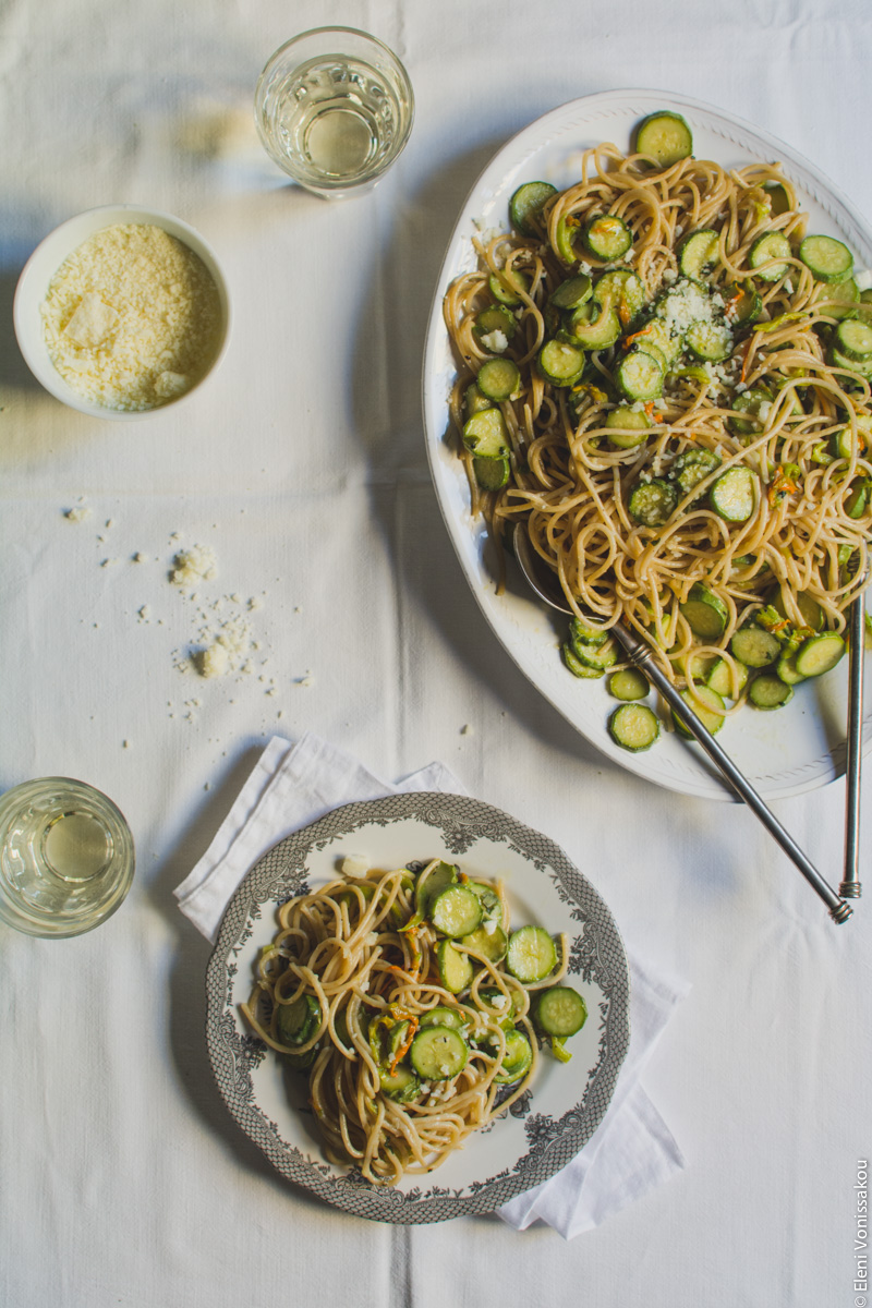Whole Wheat Courgette Pasta with Courgette Flowers www.thefoodiecorner.gr Photo description: The platter of spaghetti in the top right corner, and a small plate with a pattern around the edge in the bottom centre of the photo. The plate is sitting on a folded linen napking, and has some courgette pasta on it. The serving spoons are lying in the large platter. To the top left of the photo is a glass of wine and a small bowl of grated cheese. There another glass of wine next to the plate on its left.