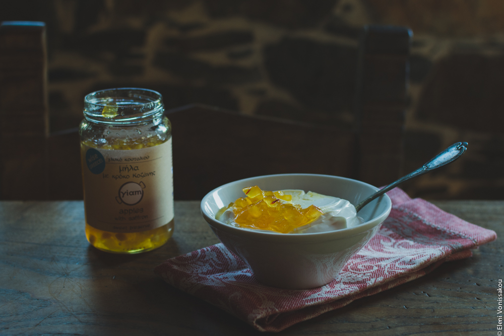 "Milia Workshop 2017 – A long overdue recap. Part 1. www.thefoodiecorner.gr - Photo description: A bowl of yoghurt with a dollop of yellow, jam like ""spoon sweet"" on top. A spoon is sitting in the yoghurt. To the left, the jar of spoon sweet. The bowl is sitting on a folded napkin with a pretty pattern, all on a wooden table. In the background a stone wall is visilble."