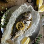 Gilt Head Bream (Dorade) – How to cook a whole fish in the slow cooker www.thefoodiecorner.gr Photo description: A cooked whole fish, lying on baking paper on a metallic plate. On it is a slice of lemon and a couple of sprigs of oregano, both cooked down and wilted. To the top left of the photo a ball of string, to its right a vintage pair of scissors, further to the right a couple of wedges of lemon. In the bottom right corner a small ceramic bowl of salt and a sprig of fresh oregano. Some more lemon wedges and oregano are around the fish to decorate it. Everything is on a wooden surface.