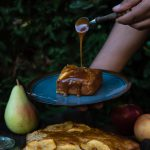 Easy, No Mixer Apple Cake with Salted Caramel Sauce www.thefoodiecorner.gr Photo description: A plate with a piece of cake on it being held above a small table outdoors. A hand is pouring caramel over the cake from a small spoon. On the table below is the cake, some apples, a pear and a knife. In the background is some dense foliage.