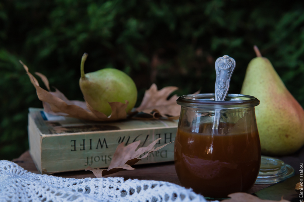 Easy, No Mixer Apple Cake with Salted Caramel Sauce www.thefoodiecorner.gr Photo description: Side view of a small jar of caramel sauce on a wooden table with a pretty spoon in it. Just behind it and to its left is a worn book with some brown leaves on it and a pear. Another pear is in the background.