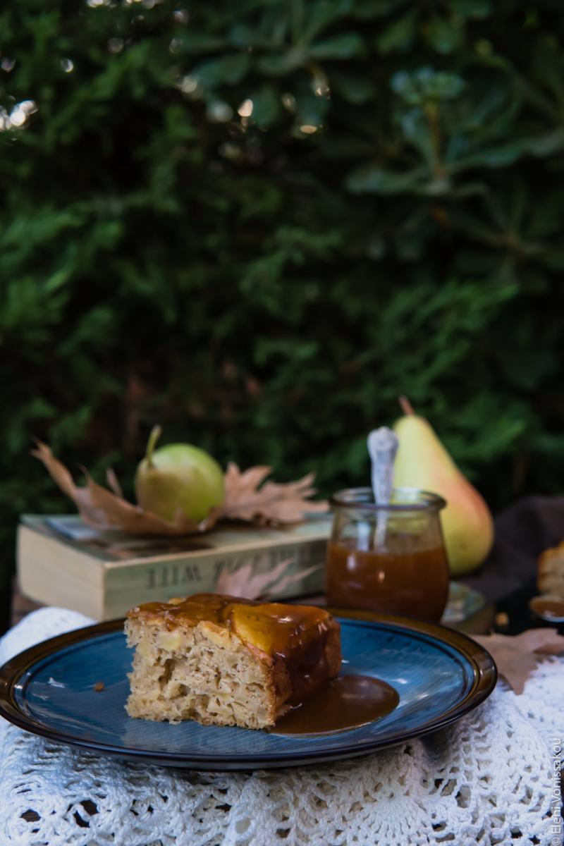 Easy, No Mixer Apple Cake with Salted Caramel Sauce www.thefoodiecorner.gr Photo description: A side view of a piece of cake on a plate. The inside of the cake is facing us and there is some caramel dripping over the other side. In the background a book, some pears and some brown leaves. All against a backdrop of dense foliage.
