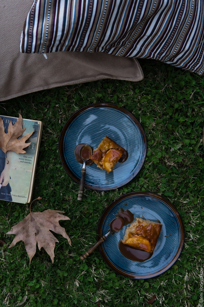 Easy, No Mixer Apple Cake with Salted Caramel Sauce www.thefoodiecorner.gr Photo description: A top view of two plates with cake on them. They are sitting on the grass, a book and some brown leaves next to them. Barely visible are two cusions.