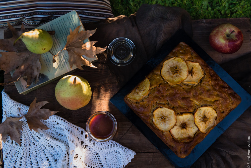 Easy, No Mixer Apple Cake with Salted Caramel Sauce www.thefoodiecorner.gr Photo description: A cake on a small table oudoors. Next to it are some apples and pears, a jar of caramel sauce, a book and some brown leaves. On one corner of the table is a small folded crocheted tablecloth.