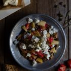 Baked Potato Dakos Salad, with Barley Rusks, Tomato and Feta www.thefoodiecorner.gr Photo description: Top view of a metalic plate filled with dakos potato salad, the feta scattered over the top with capers and sea fennel garnishing it. To the bottom right of the photo some cut up tomato, to the left some pieces of rusk, to the top left a small white bread board with some feta lying on some baking paper. Scattered on the wooden surface to the top right of the plate are some capers.