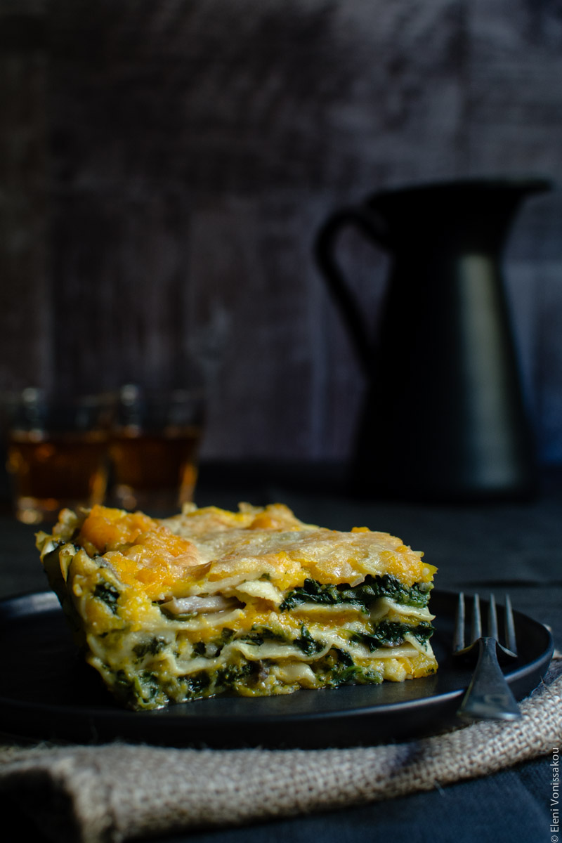 Cottage Cheese Vegetable Lasagne with Butternut Squash, Spinach and Mushrooms www.thefoodiecorner.gr Photo description: Another side shot of the cut piece of lasagna, from a slightly bigger distance. There is a fork lying on the plate next to it.